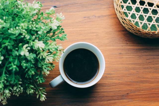 Une tasse de café sur une table en bois.